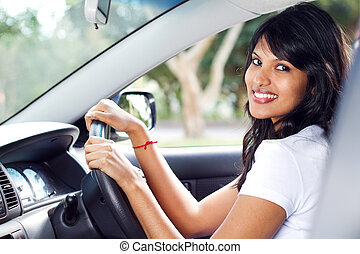 young woman driving a car - young indian woman driving a car...