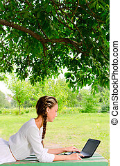 Young beauty with notebook - Pretty woman is laying on a...