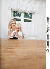 Mother with baby boy looking at bread - Smiling young mother...