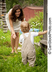 First Steps - Mother urges a small sonny to make the first...