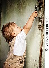 Kid and door - Year-old child pulls the door handle and...