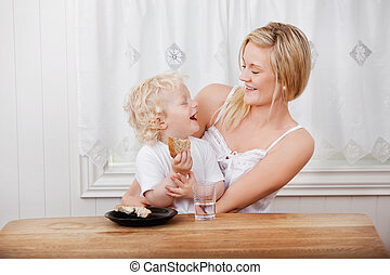 Mother looking at boy eating bread - Young beautiful mother...