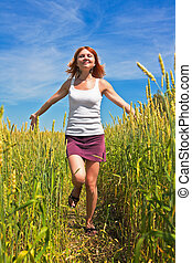 Beautiful young woman running through a wheat field in...