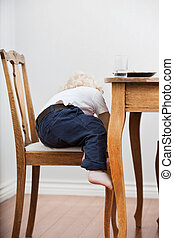 Child trying to get down from chair