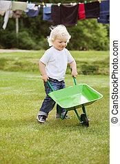 Boy pushing a wheelbarrow - Cute young baby boy pushing a...