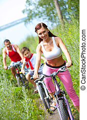 Cycling wife - Young woman riding bike with her son and...