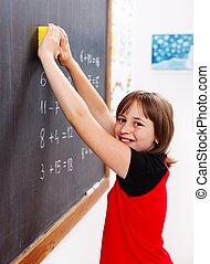 Elementary school student erasing chalkboard - Happy...