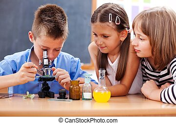 Boy looking into microscope - Eminent elementary school boy...