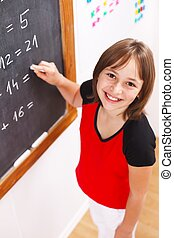 Schoolgirl looking up in front of chalkboard
