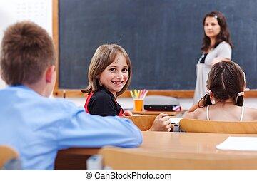 Cheerful schoolgirl in class room