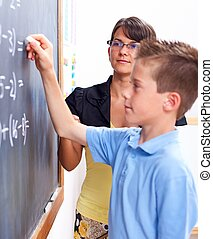 Boy writing on chalkboard in front of teacher