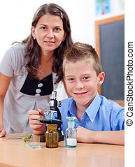 Wise boy with microscope and teacher