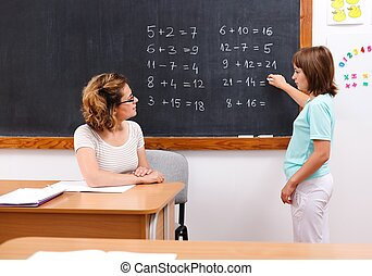 Schoolgirl solving math equations at chalkboard - Elementary...