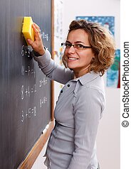 Teacher erasing chalkboard with sponge - Cheerful teacher...
