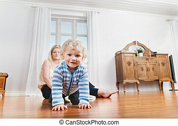 Baby crawling with mother in the background - Portrait of...
