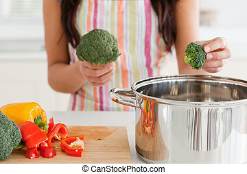 Female preparing vegetables while standing in the kitchen
