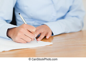 Frontal view of a young woman writing on a sheet of paper...
