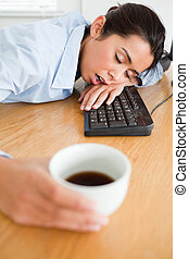 Gorgeous woman sleeping on a keyboard while holding a cup of...