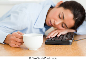 Beautiful woman sleeping on a keyboard while holding a cup...
