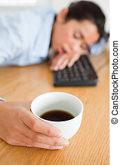 Cute woman sleeping on a keyboard while holding a cup of...