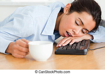 Pretty woman sleeping on a keyboard while holding a cup of...