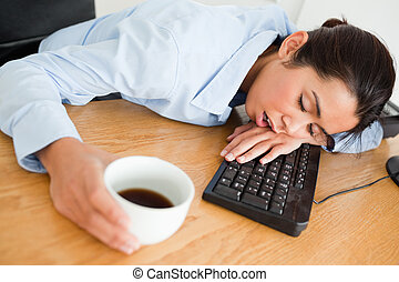Attractive woman sleeping on a keyboard while holding a cup...