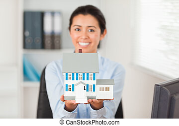 Lovely woman holding a miniature house while looking at the...