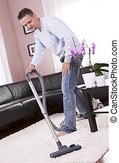 Living room cleaning vacuum cleaner - Man in the modern...