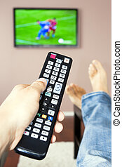Men with the remote control, front of the television - Young...