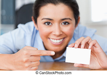 Attractive woman showing her visiting card at the office