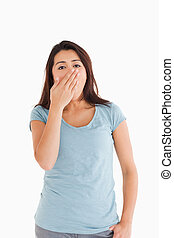 Beautiful tired woman yawning while standing against a white...