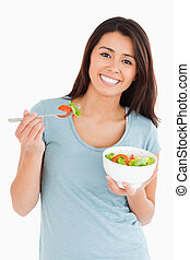 Good looking woman eating a bowl of salad