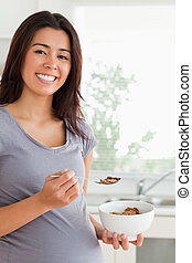 Gorgeous pregnant woman enjoying a bowl of cereals while...