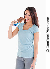 Attractive woman eating a chocolate bar
