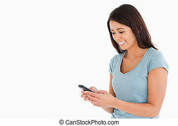 Attractive woman writing a text on her mobile phone while...