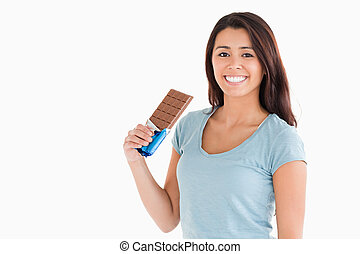 Lovely female holding a chocolate bar while standing against...
