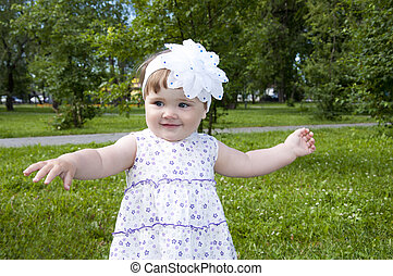 cute little girl dancing in the park, background green grass...