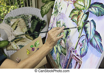 beautiful blond artist in her fifties painting a still life...