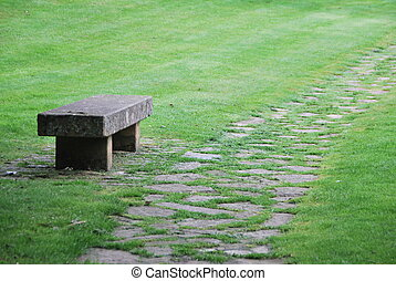 Solitary stone bench - View of a stone bench and path with...