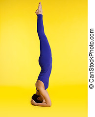 woman exercise yoga stand on head - blue and yellow
