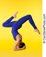 Young woman doing yoga pose - stand on head - woman stand on...