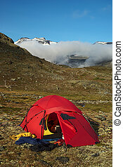 Tent and drying clothes in the Jotunheimen National Park, Norway with the Galdhopiggen covered by clouds in the back