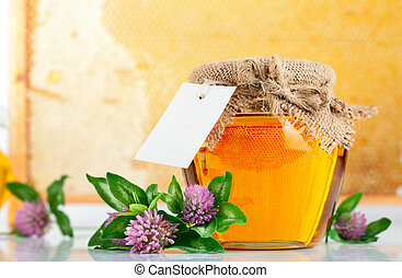 sweet honey in glass jars with flowers isolated on white...