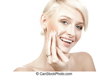 calm beauty portrait of a smiling young woman putting cream