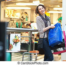 Cute brunette girl smiling on shopping