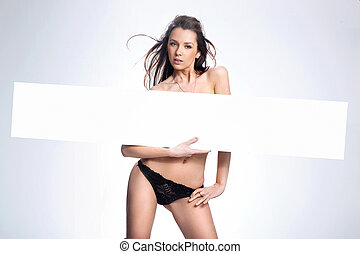 Young beautiful brunette holding empty whiteboard