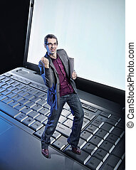Conceptual photo of a happy man standing on the laptop's keyboard