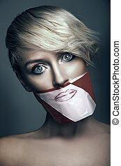 Conceptual photo of woman with the mouth taped up