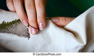 Needlework. - Woman hands doing cross-stitch. A close up of...