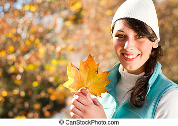 fall - young woman holding golden tree leaf outdoor in fall...